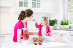 Toddler girl and adorable mother making fresh strawberry Stock Photos
