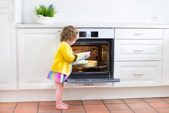 Toddler girl with an apple pie in the oven Stock Photography