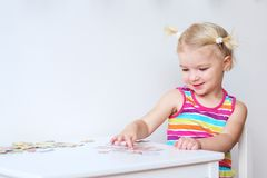 Toddler girl assembling jigsaw puzzle indoors Stock Photography