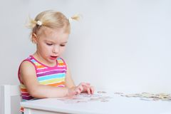 Toddler girl assembling jigsaw puzzle indoors. Happy little child, adorable blonde toddler girl, having fun playing with jigsaw puzzle assembling pieces of Royalty Free Stock Photography