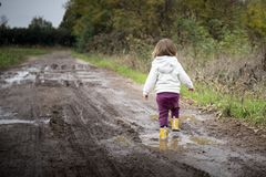 Toddler splashing in puddles in muddy country road. Toddler girl, back view, splashing in puddles in muddy country road with yellow rain boots. Left copy space royalty free stock photos