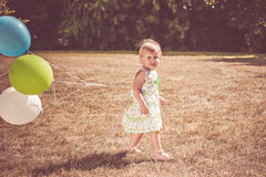 Toddler girl with balloons in park Royalty Free Stock Photo