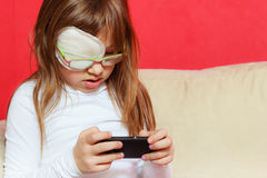 Toddler girl with bandage on eye playing games Royalty Free Stock Photo