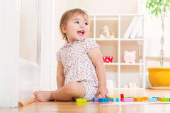 Toddler girl with a big smile playing with wooden toy blocks Stock Photo