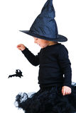 Toddler girl in black little witch costume. Halloween dressed toddler girl in black little witch costume looking to small spider royalty free stock photography