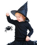 Toddler girl in black little witch costume. Halloween dressed toddler girl in black little witch costume looking to small spider stock images