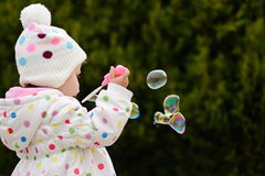 Toddler girl blowing soap bubbles Stock Photography