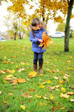 Toddler girl in blue coat picking up leaves Royalty Free Stock Photo