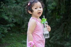 Toddler girl with bottle of water. Side view of a toddler girl holding bottle of water outdoors Royalty Free Stock Images