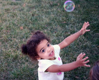 Toddler Girl Bubbles. Two year old girl outside with bubbles Royalty Free Stock Images