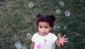 Toddler Girl Bubbles. Two year old girl outside with bubbles Stock Photo