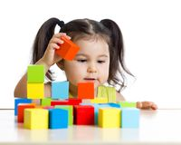 Toddler girl builds a tower with colorful blocks Stock Photography