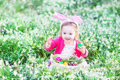 Toddler girl in bunny ears with eggs in first spri Royalty Free Stock Photos