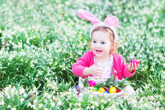 Toddler girl in bunny ears with eggs in spring flowers Royalty Free Stock Image
