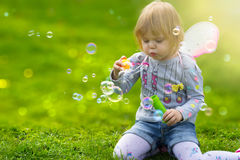 Toddler girl with butterfly wings having fun in park Stock Photo
