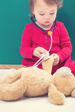Toddler girl caring for her teddy bear with a stethoscope Stock Photo