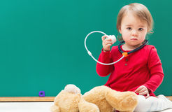 Toddler girl caring for her teddy bear with a stethoscope Stock Photos