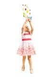 Toddler girl catching toys Stock Photos