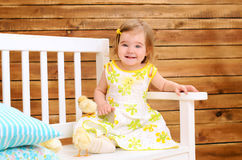Toddler girl with chickens on bench indoors Royalty Free Stock Photo