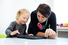 Toddler girl in child occupational therapy session doing playful exercises on a digital tablet with her therapist. royalty free stock images