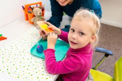Toddler girl in child occupational therapy session doing sensory playful exercises with her therapist. royalty free stock photo