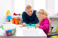 Toddler girl in child occupational therapy session doing sensory playful exercises with her therapist. Toddler girl in child occupational therapy session doing royalty free stock photos