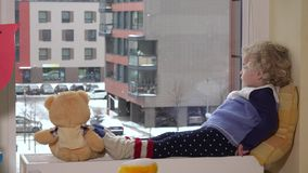 Toddler girl child talk with teddy bear excited to see snow outside stock video footage
