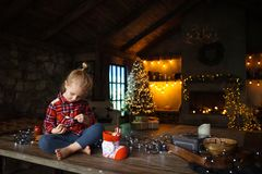 Little white blonde girl sitting on a wooden table in the living room of the Chalet, decorated for Christmas tree and garlands wit royalty free stock image
