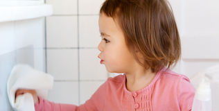 Toddler girl cleaning the kitchen Royalty Free Stock Image