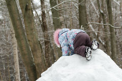 Toddler girl climbing top of snowy hill in Royalty Free Stock Photo