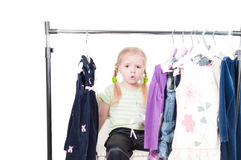 Toddler girl and clothes. Shot of cute toddler girl choosing clothes stock photo