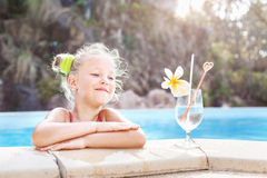 Toddler girl with cocktail in tropical beach pool. Little girl with cocktail in tropical beach pool. Outdoors Royalty Free Stock Photo
