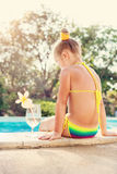 Toddler girl with cocktail in tropical beach pool Stock Image