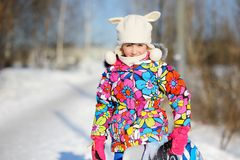 Toddler girl in colorful snowsuit plays in snow Royalty Free Stock Photography