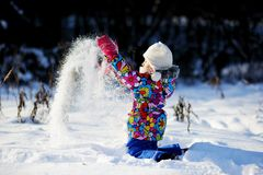 Toddler girl in colorful snowsuit plays in snow Royalty Free Stock Images