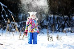 Toddler girl in colorful snowsuit plays in snow Royalty Free Stock Photo