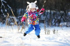 Toddler girl in colorful snowsuit plays in snow Royalty Free Stock Photos