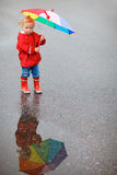 Toddler girl with colorful umbrella on rainy day Stock Image