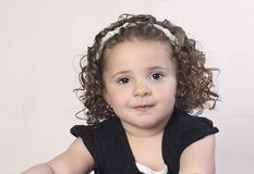 Toddler girl with curly hair and pearl headband royalty free stock images