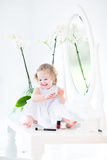 Toddler girl with curly hair playing with cosmetics Royalty Free Stock Photos
