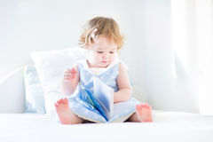 Toddler girl with curly hair wearing blue dress sitting o Stock Image