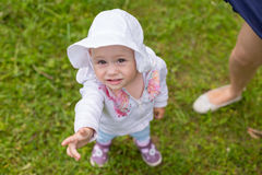 Toddler girl with cute face reaches her hand Stock Photo