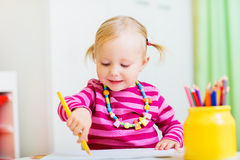 Toddler girl drawing. Adorable happy toddler girl drawing with coloring pencils, perfect for early education context royalty free stock images