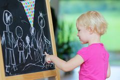 Toddler girl drawing on black board Stock Photo