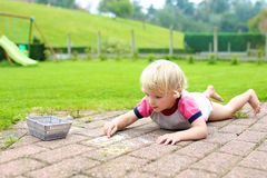 Toddler girl drawing with chalk outdoors Stock Image