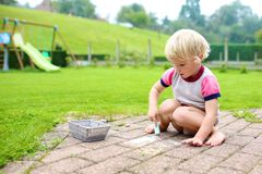 Toddler girl drawing with chalk outdoors Royalty Free Stock Images