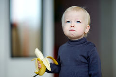 Toddler girl eating a banana Stock Photos