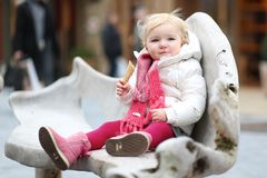 Toddler girl eating ice cream outdoors at winter Stock Photos