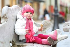 Toddler girl eating ice cream outdoors at winter Stock Images