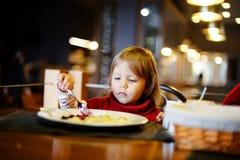 Toddler girl eating in restaurant Stock Image